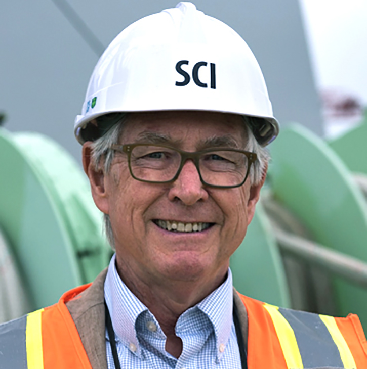 white man in construction vest smiling wearing construction hat